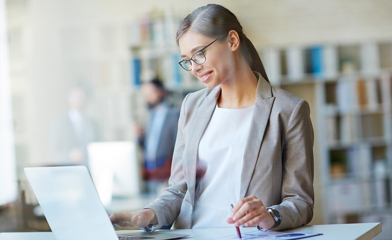 En kvinne jobber ved å stå på balansebrett under kontorpulten og hun ser veldig fornøyd ut