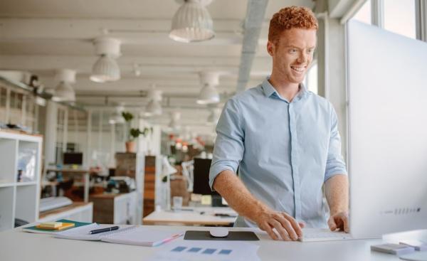 Ung mann jobber fornøyd stående på et balansebrett for kontorarbeid