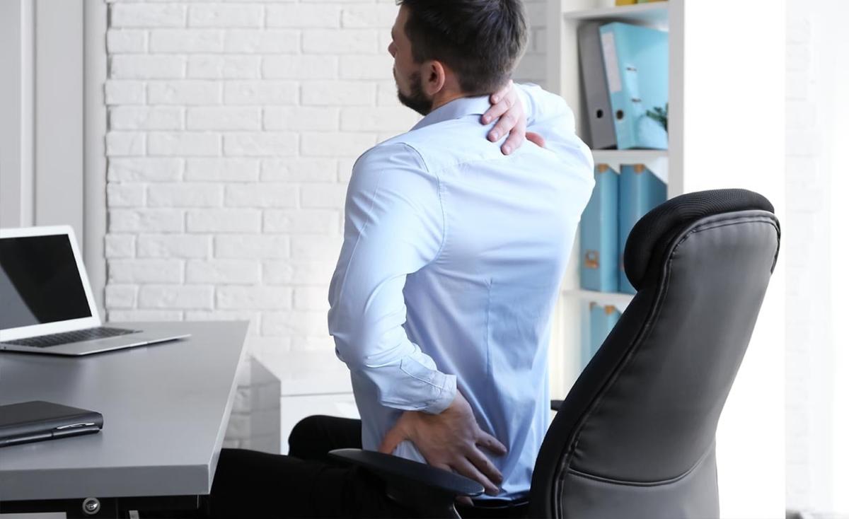 Mann sitter med nakke og ryggsmerter og kjenner på skader ved stillesitting